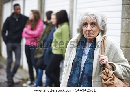 Senior Woman Feeling Intimidated By Group Of Young People - stock photo