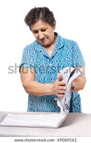 Senior woman folding the clothes, isolated on white background - stock photo