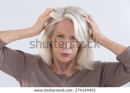 Senior woman furiously scratching her head