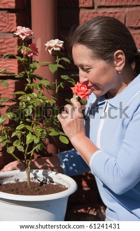 senior  woman gardener with flowers outdoor in her garden
