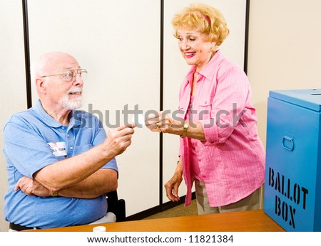Senior woman gets her I Voted sticker from a volunteer at the polling place. - stock photo
