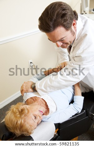 Senior woman gets relief from back pain when her chiropractor adjusts her spine. - stock photo