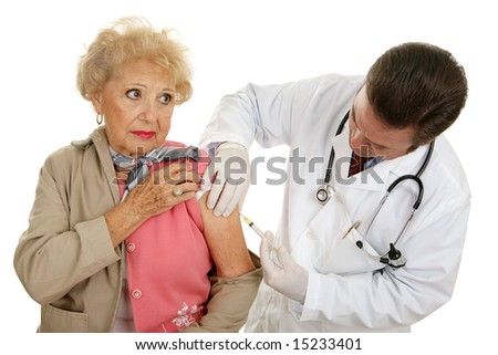 Senior woman getting a vaccination from the doctor.  Isolated on white.