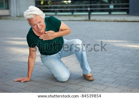 Senior woman getting heart attack in urban environment - stock photo