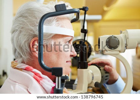 Senior woman getting her cornea checked with slit lamp at optician - stock photo