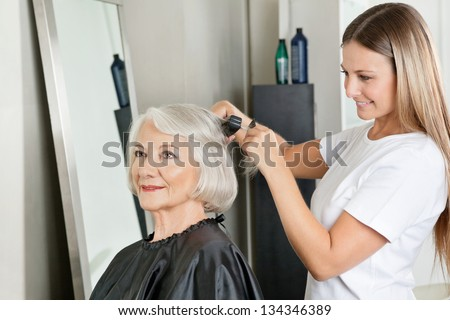 Senior woman getting her hair straightened by female hairstylist at salon - stock photo
