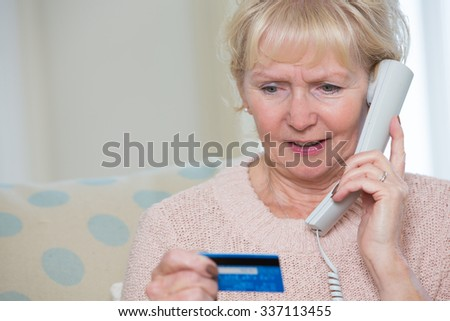 Senior Woman Giving Credit Card Details On The Phone - stock photo