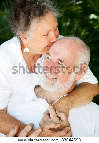 Senior woman giving her husband a kiss on the forehead. - stock photo