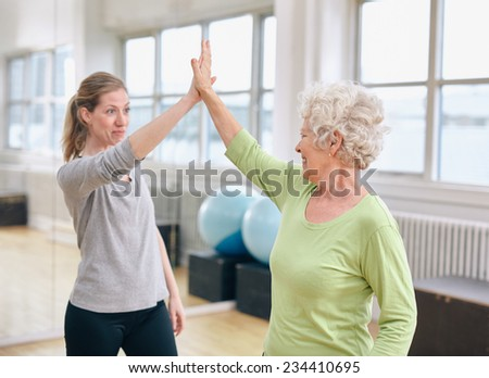 Senior woman giving high five to her personal trainer at gym. Excited old woman rejoicing health success with her instructor at rehab. - stock photo