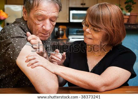 Senior woman giving man shot with small hypodermic needle - stock photo