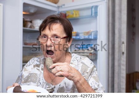 Senior woman going to eat pork liver sausage while standing in front of the open fridge in the kitchen. - stock photo