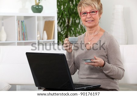 Senior woman having a coffee in front of her laptop computer - stock photo