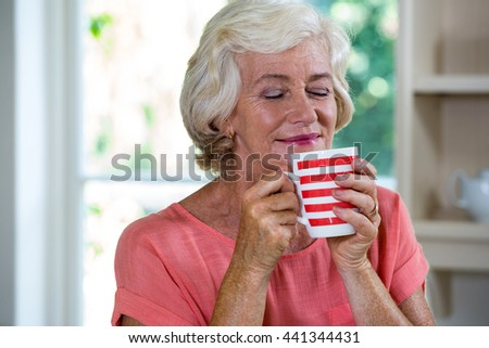 Senior woman having coffee in kitchen at home