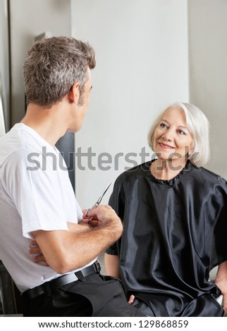 Senior woman having conversation with male hairdresser at parlor