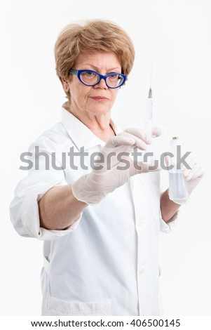 Senior woman healthcare worker looking at syringe for vaccination in her hand, white background - stock photo
