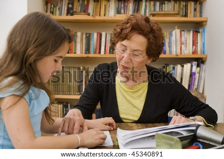 senior woman helping child doing homework - stock photo