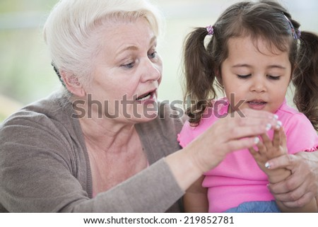 Senior woman helping granddaughter in counting fingers at home - stock photo