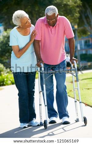 Senior Woman Helping Husband With Walking Frame - stock photo