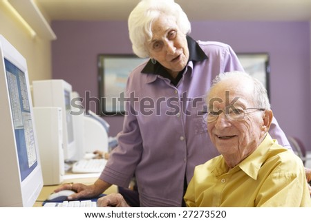 Senior woman helping senior man use computer - stock photo