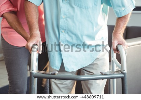 Senior woman helping senior with walking aid in a retirement home