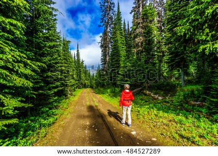 Senior woman hiking in mountains around Sun Peaks village in the Shuswap Highlands of British Columbia, Canada