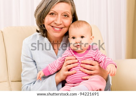 Senior woman hold little baby girl cute smiling close-up - stock photo