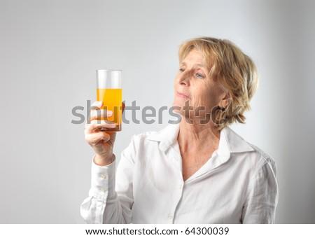 Senior woman holding a glass of orange juice - stock photo