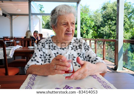 senior woman holding a glass of tea - stock photo