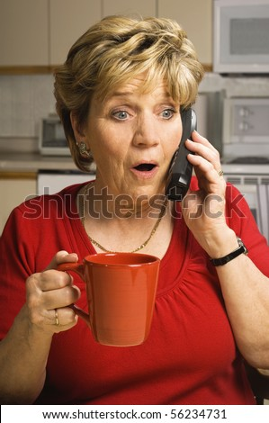 Senior woman, holding a red coffee mug, talks on the phone with a look of shock and surprise on her face.