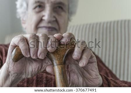 senior woman holding a wooden cane - stock photo