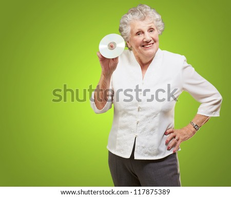 Senior woman holding cd isolated on green background - stock photo