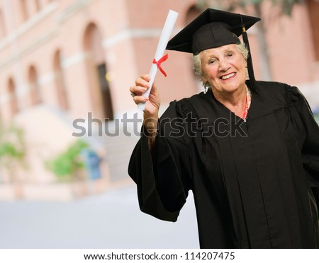Senior Woman Holding Degree In Hand, Outdoors - stock photo