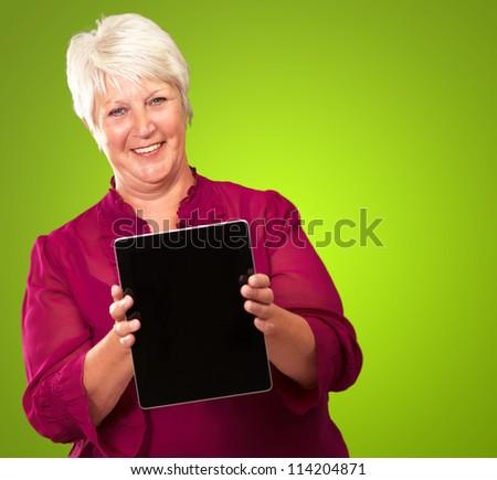 Senior Woman Holding Digital Tablet On Green Background - stock photo