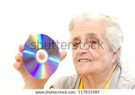 Senior woman holding dvd isolated on white background - stock photo