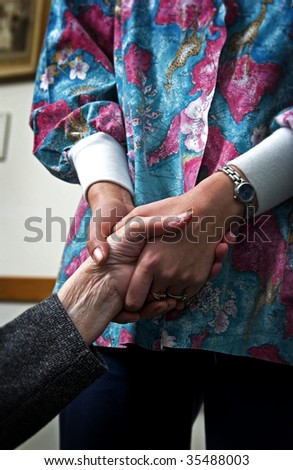 senior woman holding hand of nurse - stock photo