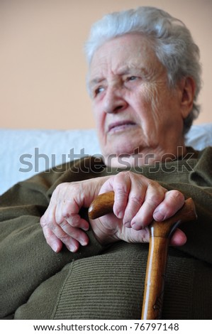 senior woman holding her cane - stock photo