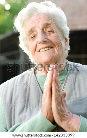 Senior woman holding her hands together - stock photo