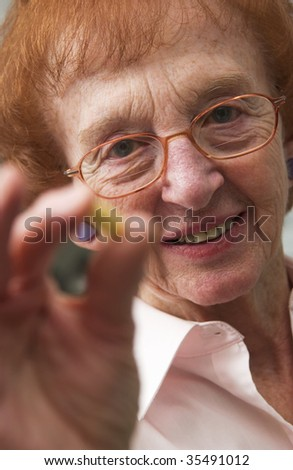 senior woman holding pills - stock photo