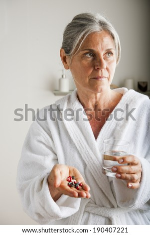Senior woman holding pills and water in her hands - stock photo
