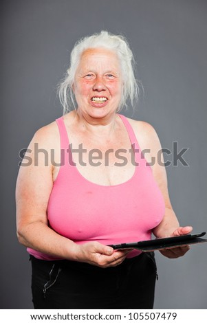Senior woman holding tablet long grey hair. Studio shot. Isolated on grey background. - stock photo