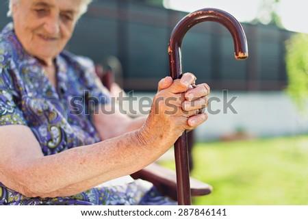 Senior woman holding walking stick - stock photo