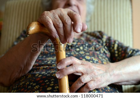 senior woman holding wooden cane