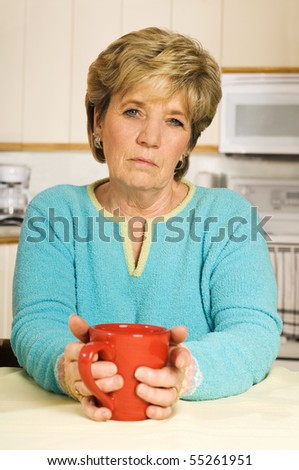 Senior woman holds a coffee mug, looking unhappy. - stock photo