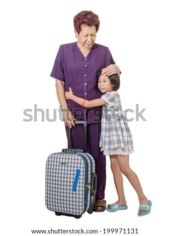 Senior woman hugging cry girl with suitcase, isolated on white. - stock photo