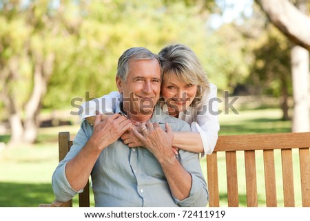 Senior woman hugging her husband who is on the bench - stock photo