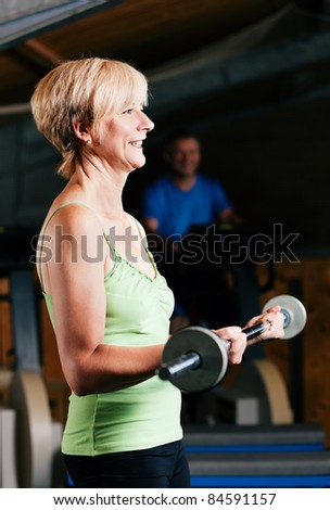 Senior woman in a gym exercising with barbell; in the background her friends - stock photo