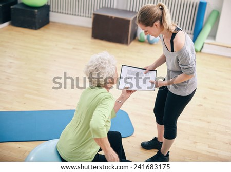 Senior woman in a gym sitting on exercise ball and talking to her private trainer about exercise plan - stock photo