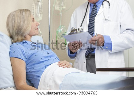 Senior woman in a hospital bed having talking to male doctor with stethoscope and clipboard - stock photo