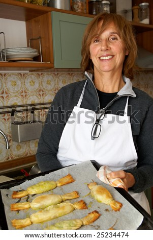 Senior woman in a kitchen, happy and proud to cook - stock photo
