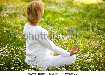 Senior woman in a lotus position in a grass with flowers - stock photo